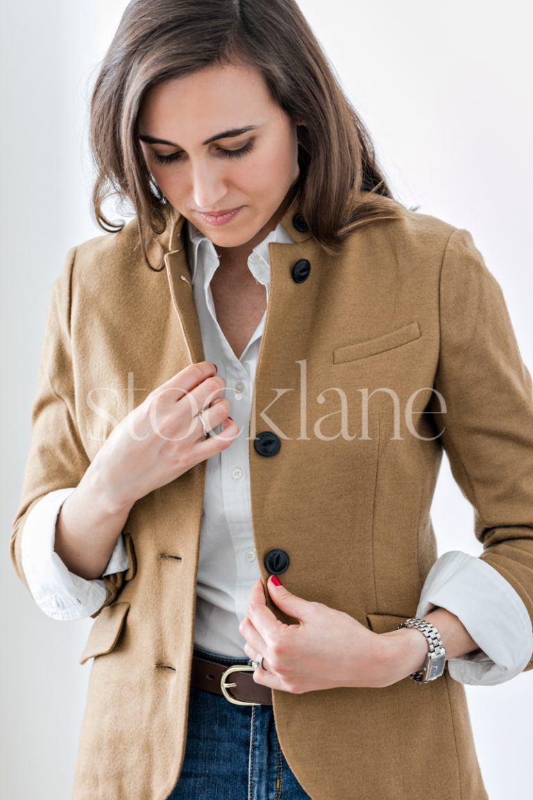 Vertical stock photo of woman adjusting her blazer.