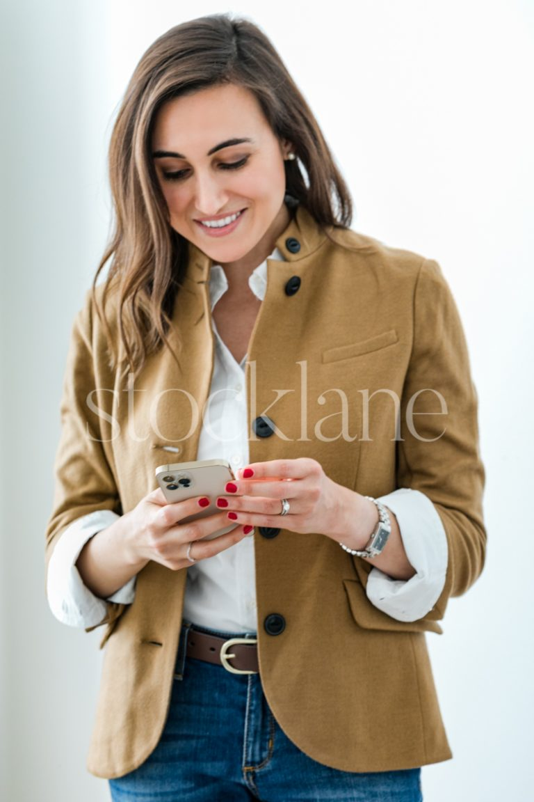 Vertical stock photo of a woman holding an iPhone.