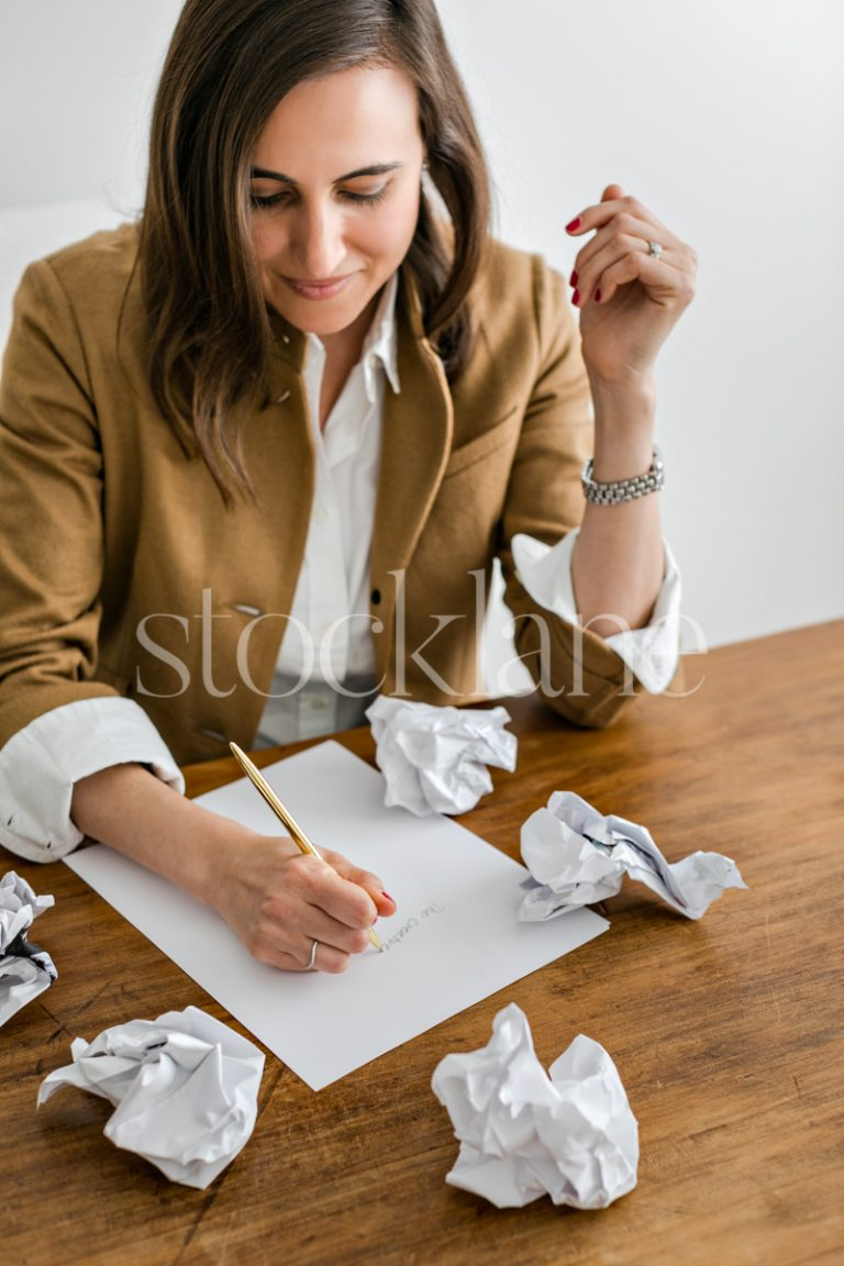 Vertical stock photo of a woman writing.