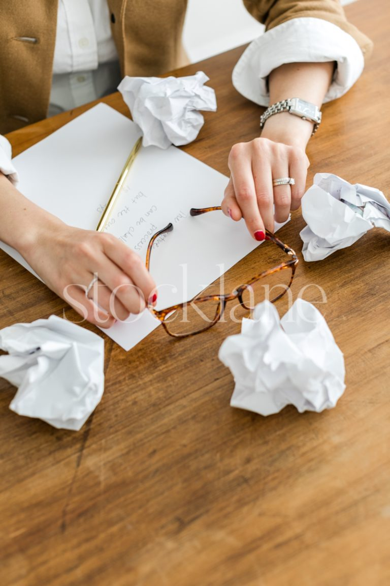 Vertical stock photo of woman writing holding her glasses.