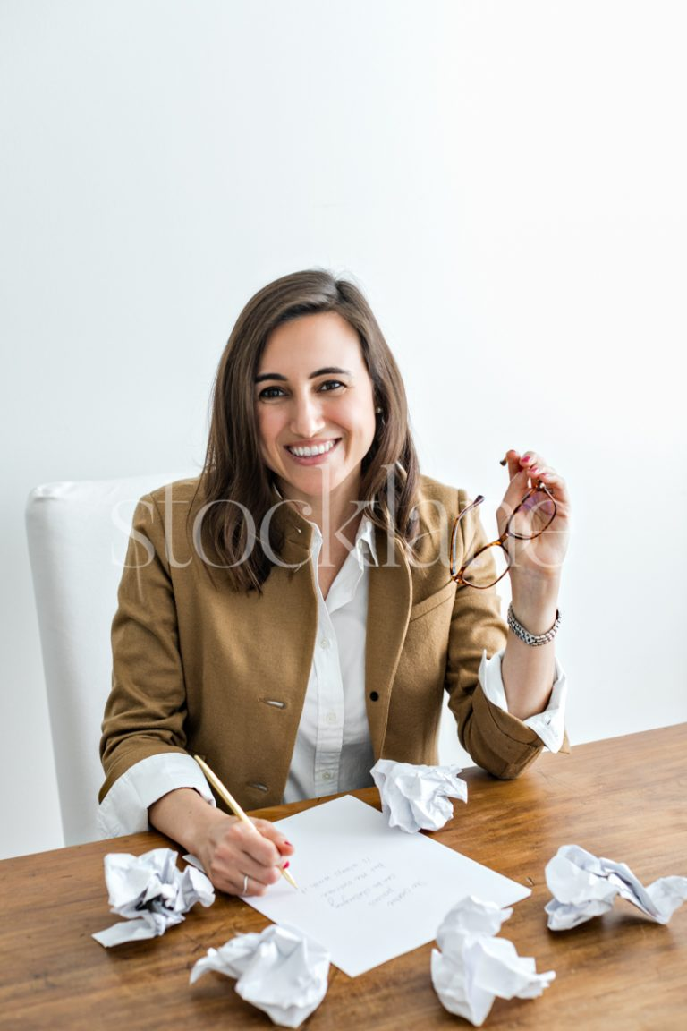 Vertical stock photo of woman writing and holding her glasses.
