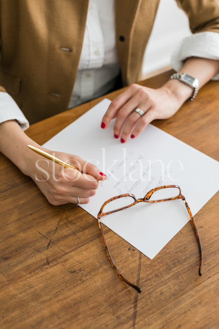 Vertical stock photo of woman writing.