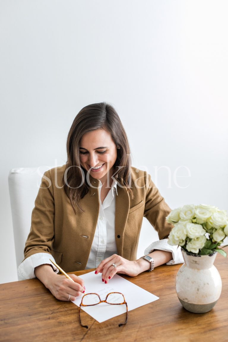 Vertical stock photo of a woman writing at her desk.