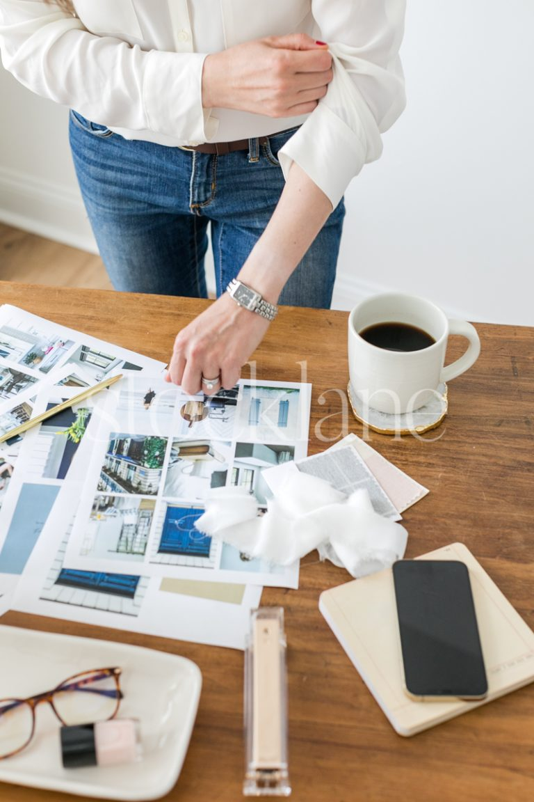 Vertical stock photo of a woman working on a mood board.