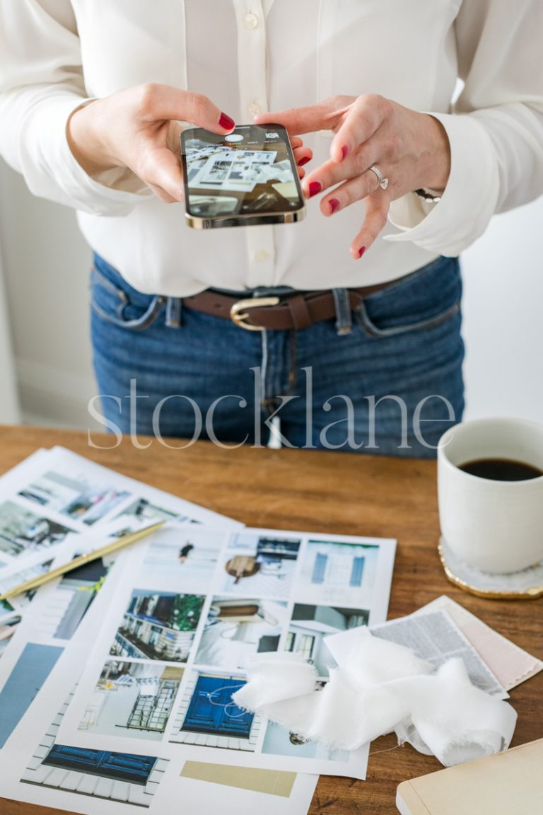 Vertical stock photo of a woman taking a photo with her phone.