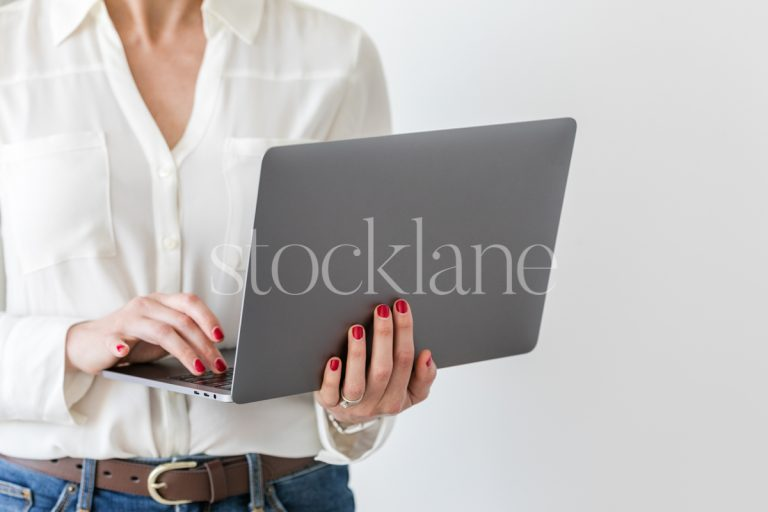 Horizontal stock photo of a woman holding a laptop computer.