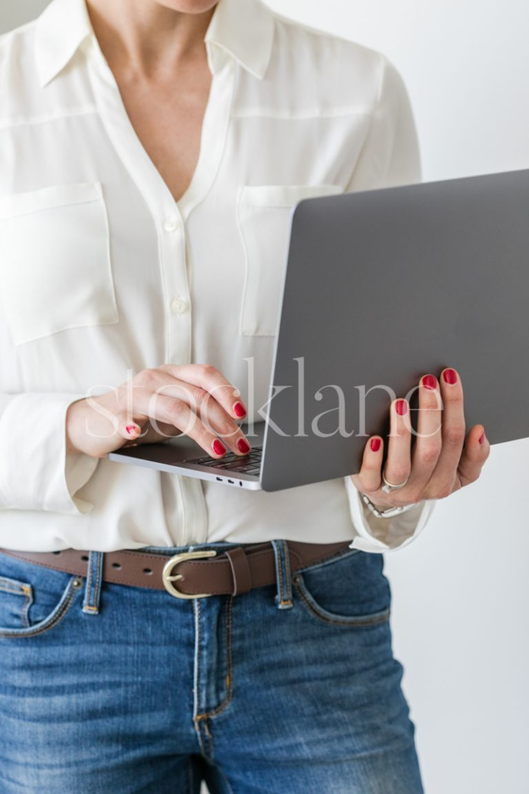 Vertical stock photo of a woman holding a laptop computer.