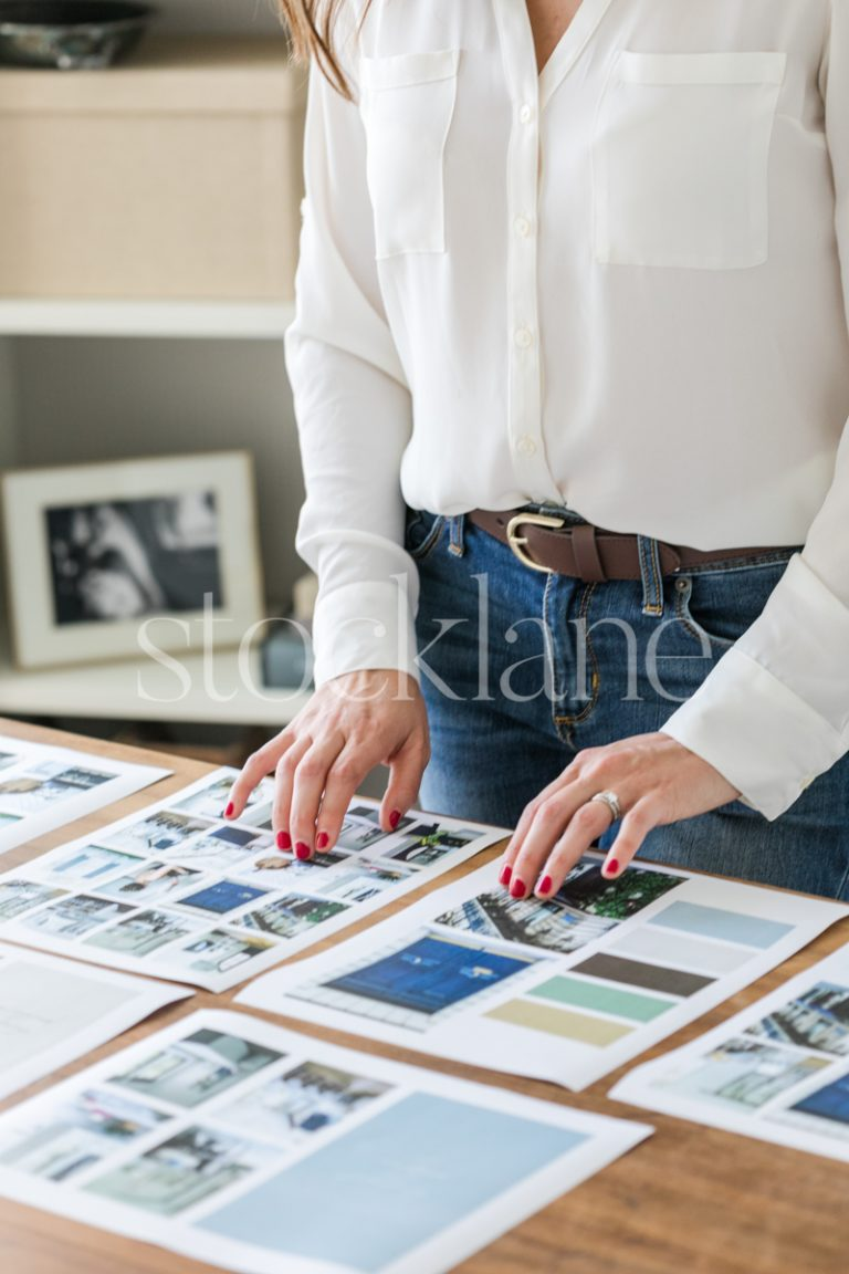 Vertical stock photo of a woman looking at mood boards on her desk.