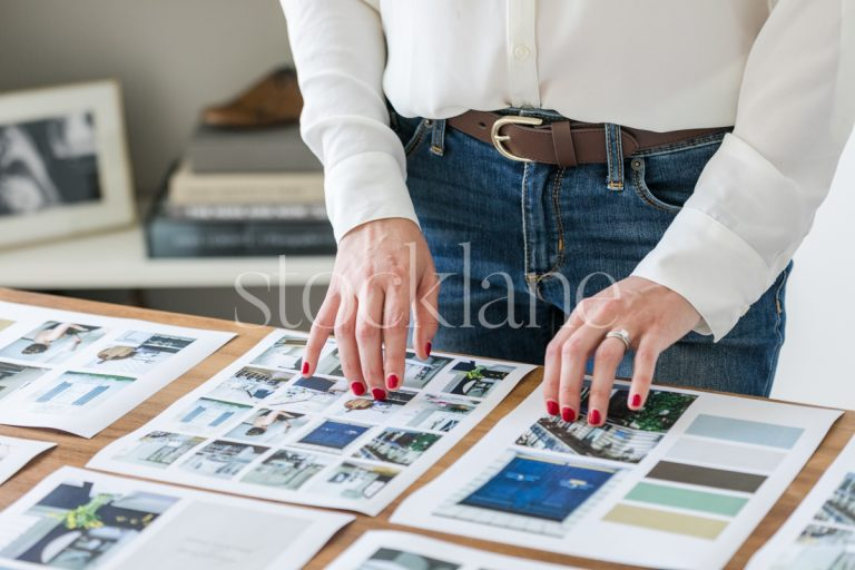 Horizontal stock photo of a woman looking at mood boards on her desk.
