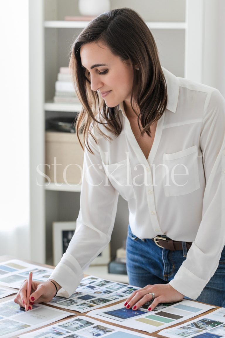Vertical stock photo of a woman working on a mood board at her desk.