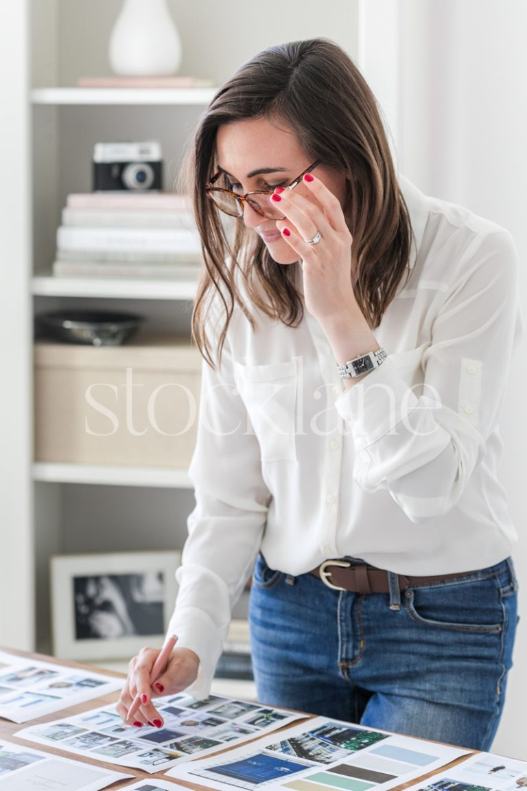 Vertical stock photo of a woman wearing glasses, working on a mood board.