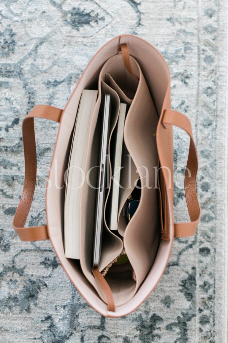 Vertical stock photo of a handbag with a computer.
