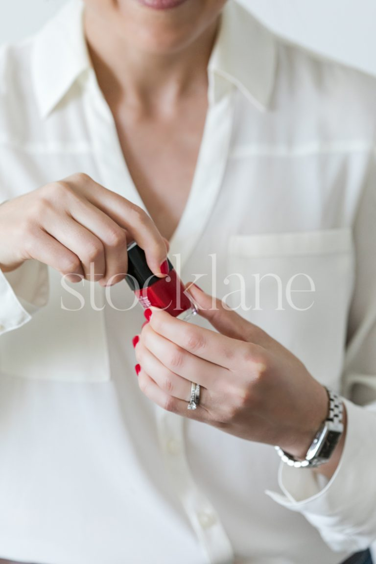 Vertical stock photo of a woman holding red nail polish.