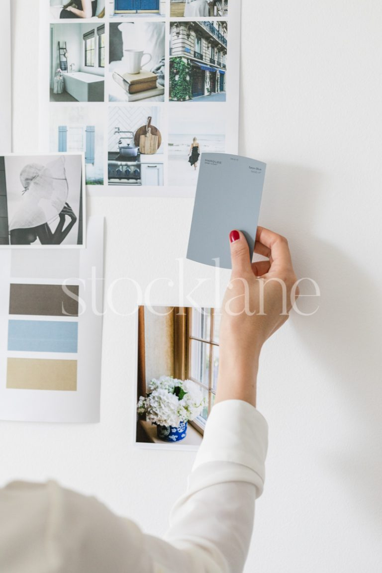 Vertical stock photo of a woman holding a color swatch to a mood board.