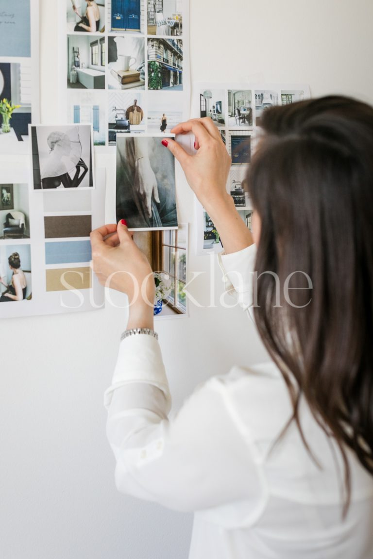 Vertical stock photo of a woman putting together a mood board.
