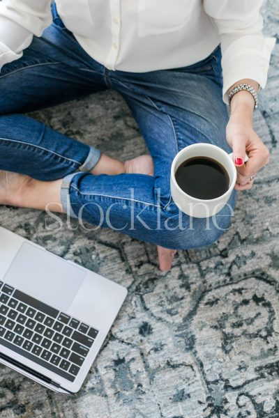 Vertical stock photo of a woman having a coffee while working at her computer.