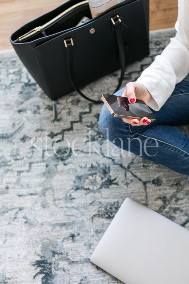 Vertical stock photo of a woman looking at her phone while working on her computer.
