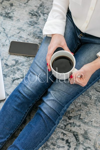 Vertical stock photo of a woman sitting on the floor drinking coffee.