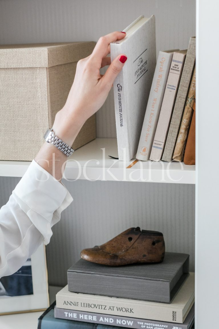 Vertical stock photo of a woman's hand picking a book from a bookcase.