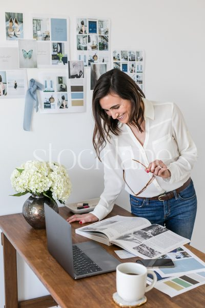 Vertical stock photo of a woman working on her laptop.