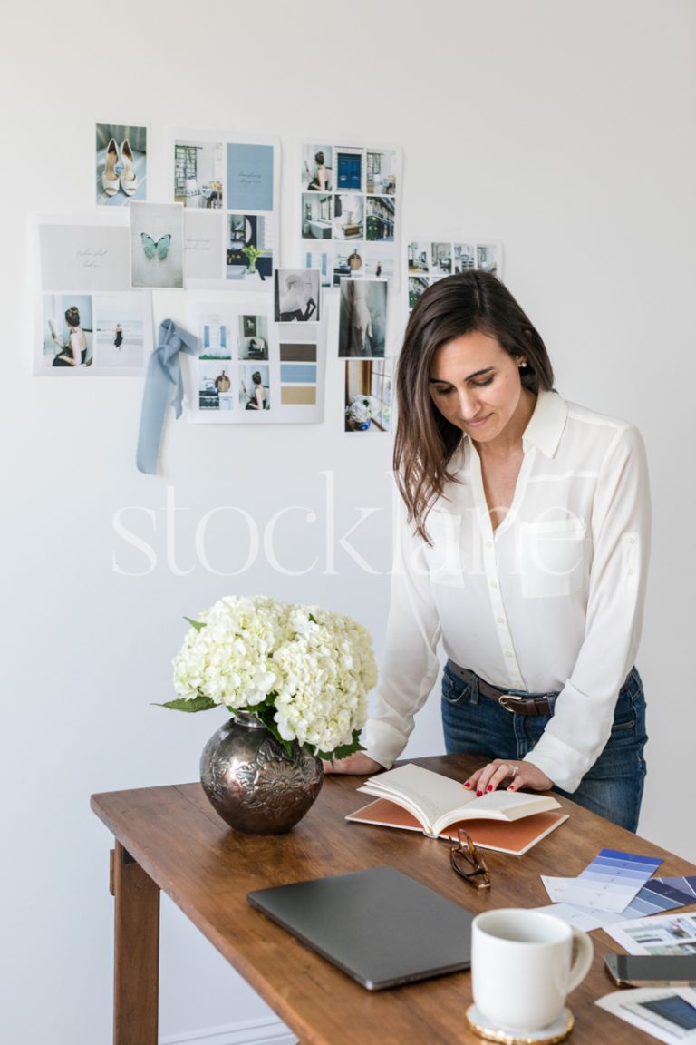 Vertical stock photo of a woman working at her desk.