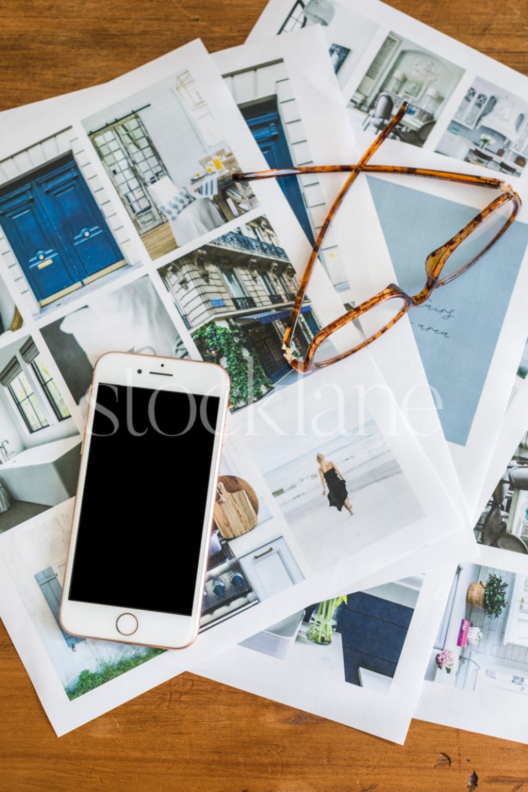 Vertical stock photo of mood board and a phone on a desk.