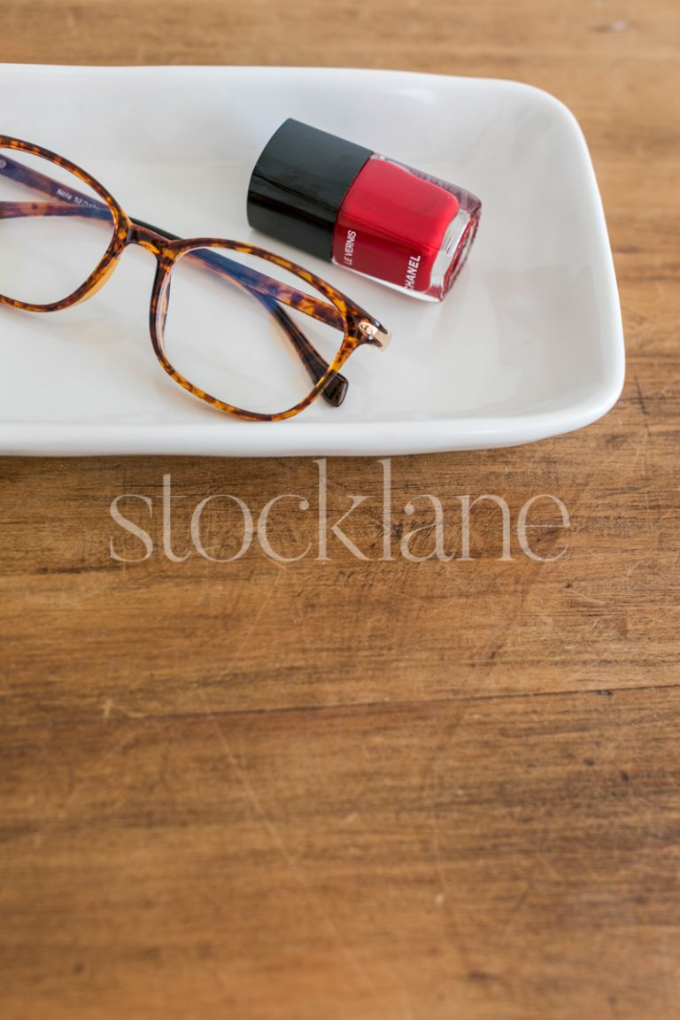 Vertical stock photo of a desk with glasses and red nail polish.