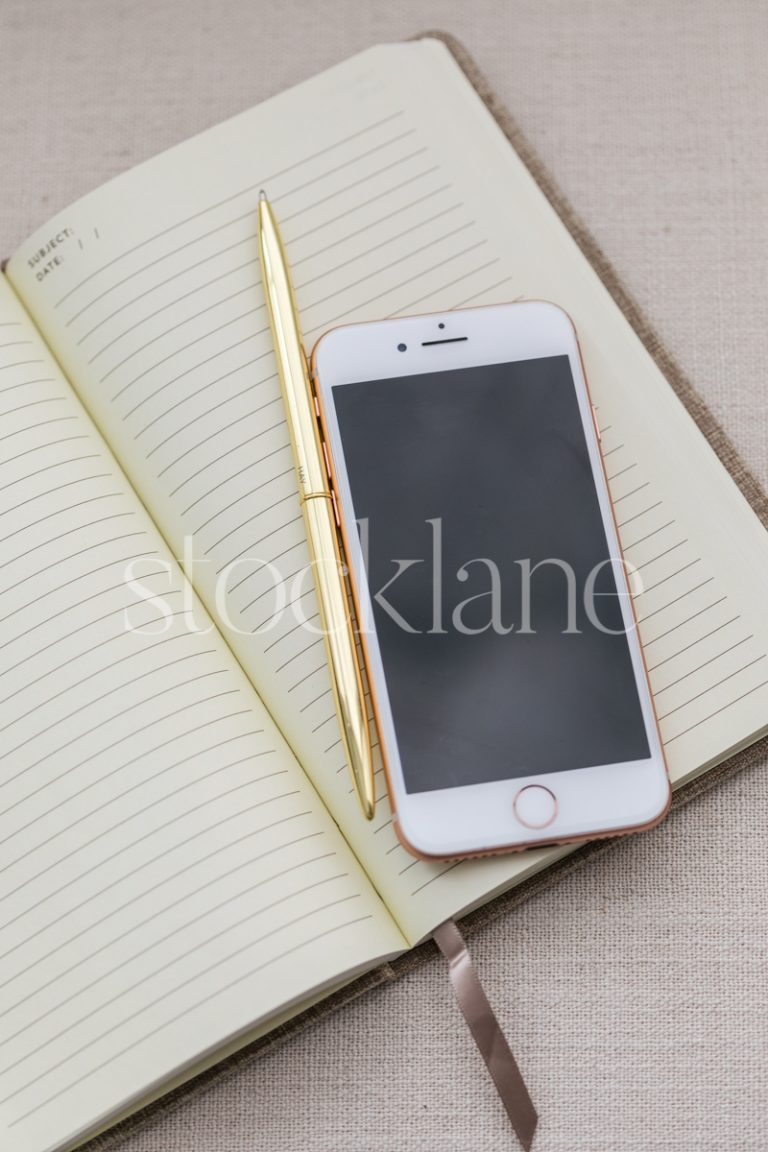 Vertical stock photo of a notebook and a phone.