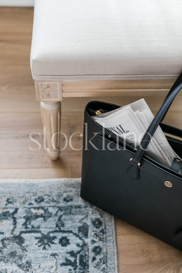 Vertical stock photo of a black handbag with a newspaper.
