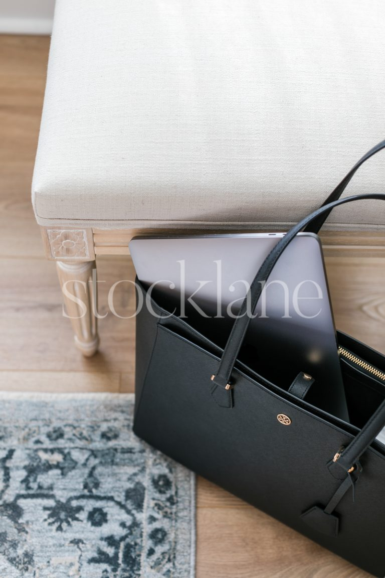 Vertical stock photo of a black handbag with a computer.