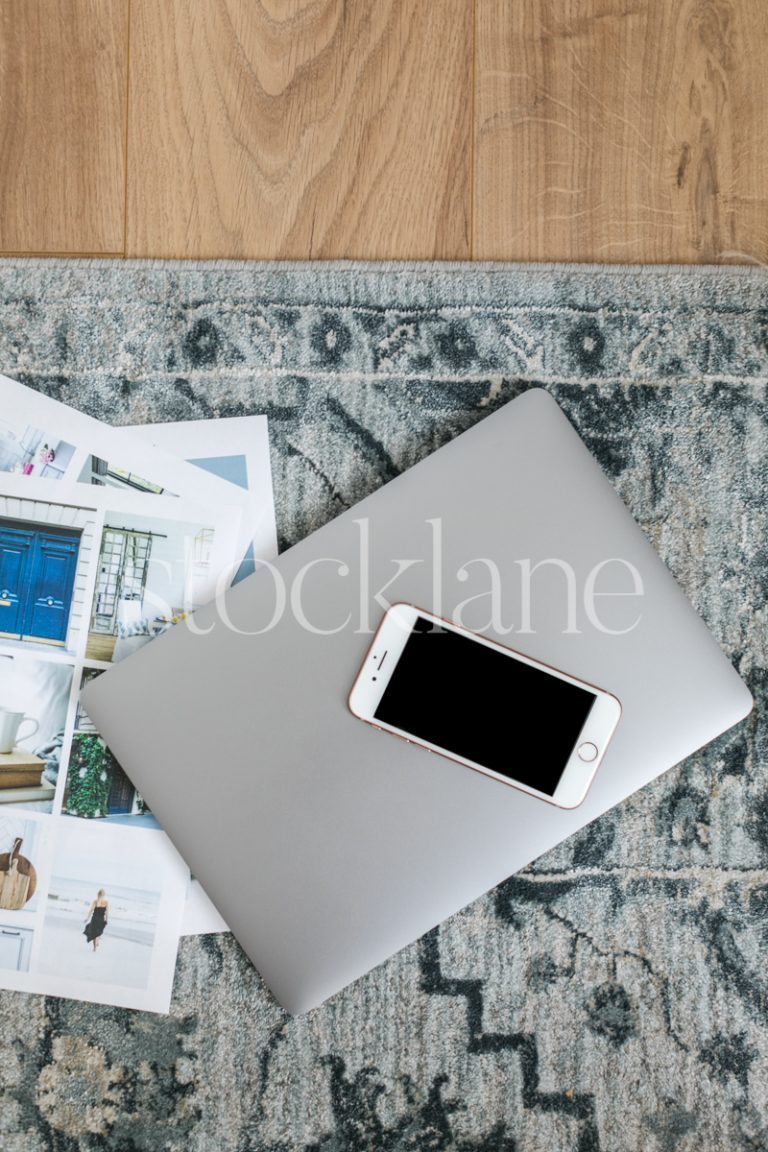 Vertical stock photo of a laptop and a phone on the floor.