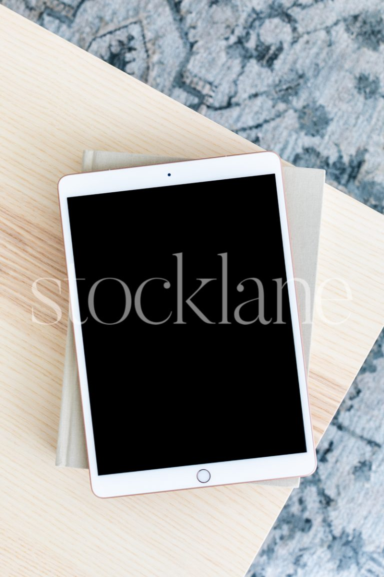Vertical stock photo with an overview of an iPad on a table in neutral colors.