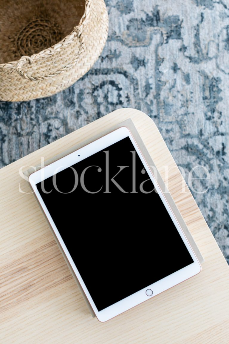 Vertical stock photo of an iPad on a neutral color table.