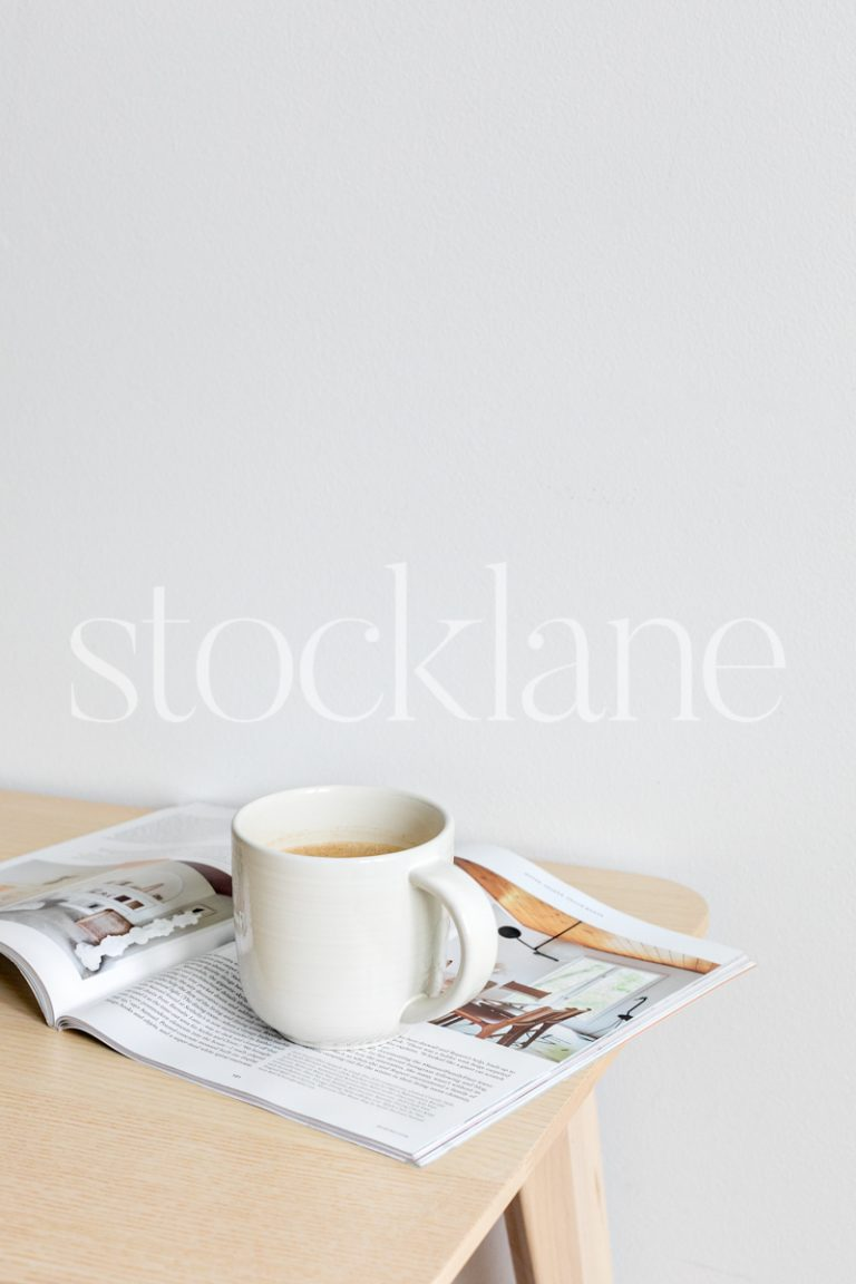Vertical stock photo of a cup of coffee and a magazine on a table.