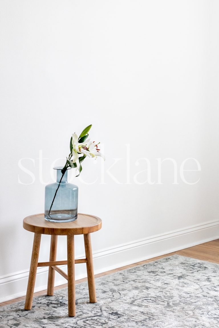 Vertical stock photo of a blue vase with asian lilies on a wood table.