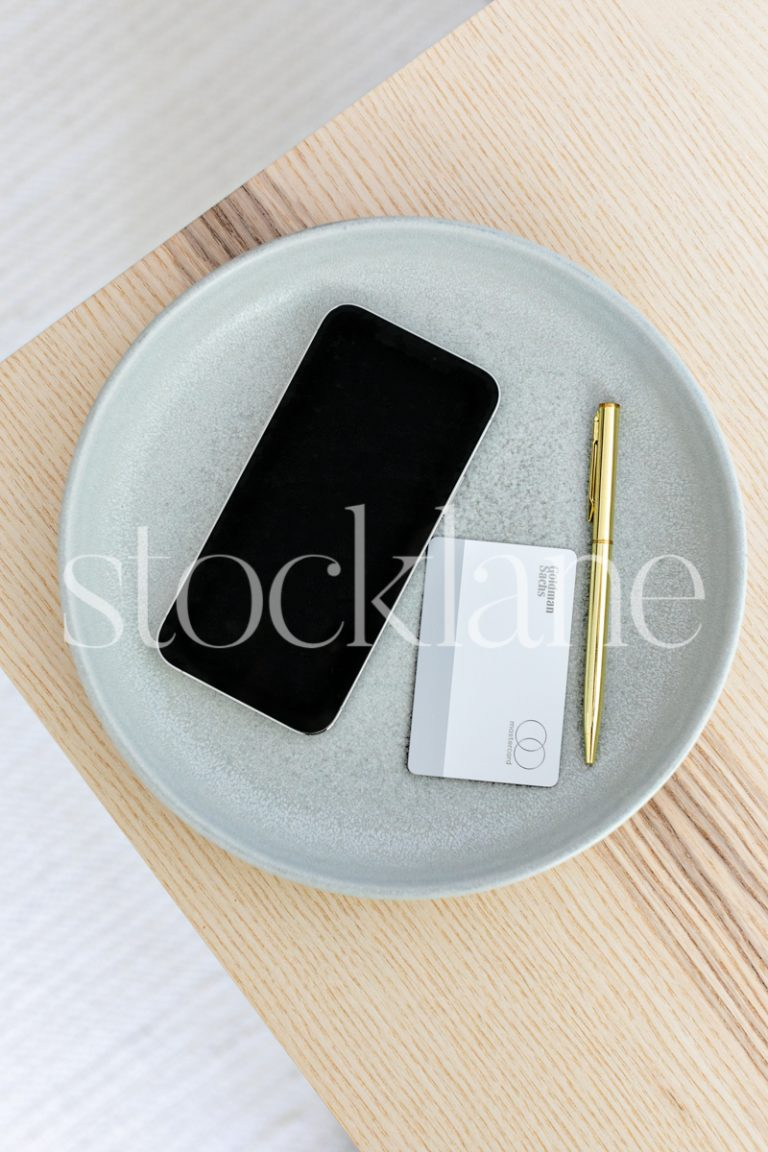 Vertical stock photo of a phone on a light green colored plate.