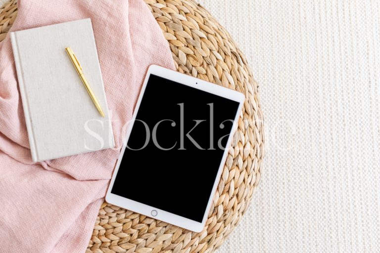 Horizontal stock photo of a tablet mockup in neutral and pink colors.