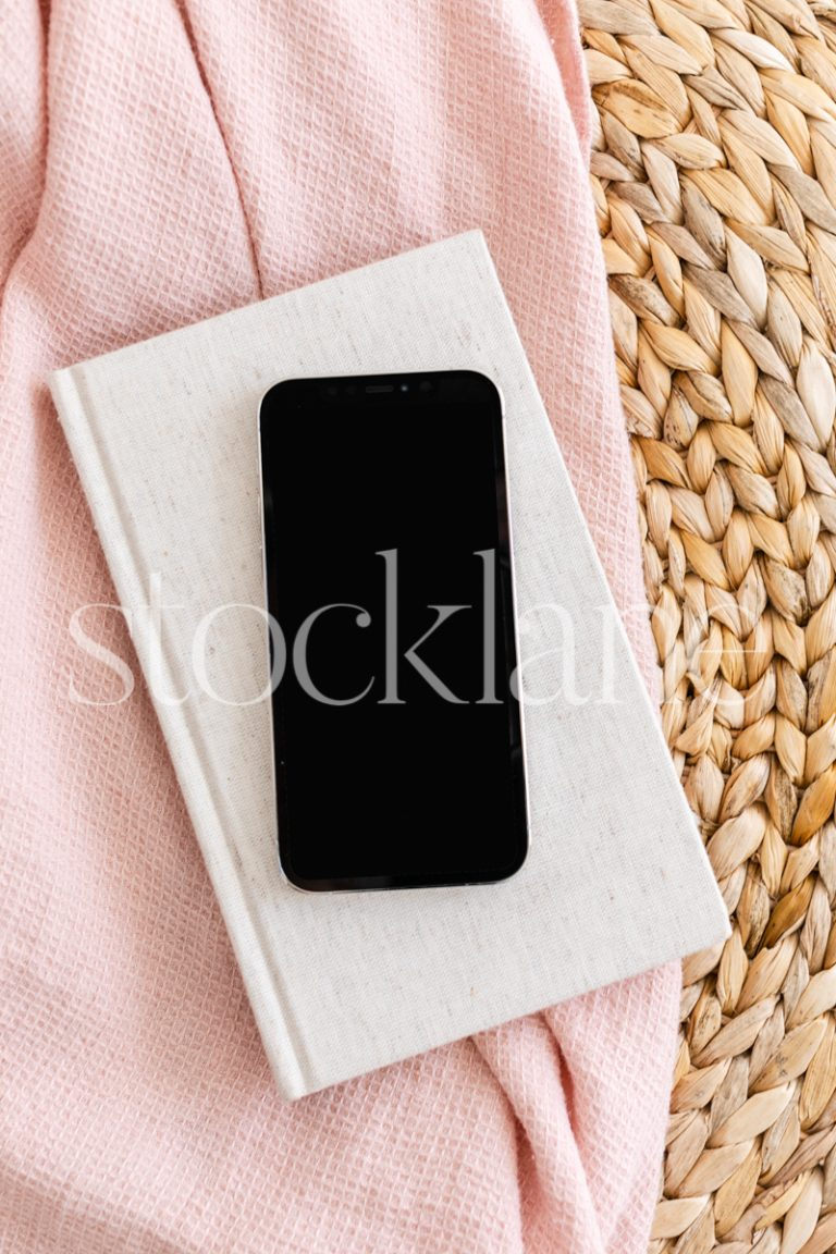 Vertical stock photo of a phone mockup in neutral and pink colors.