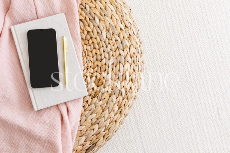 Horizontal stock photo of a phone mockup in neutral and pink colors.