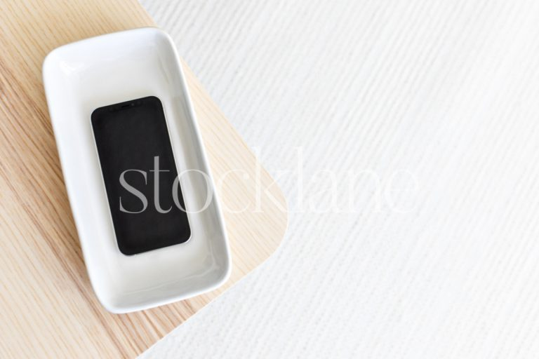 Horizontal stock photo of a phone mockup in neutral colors.