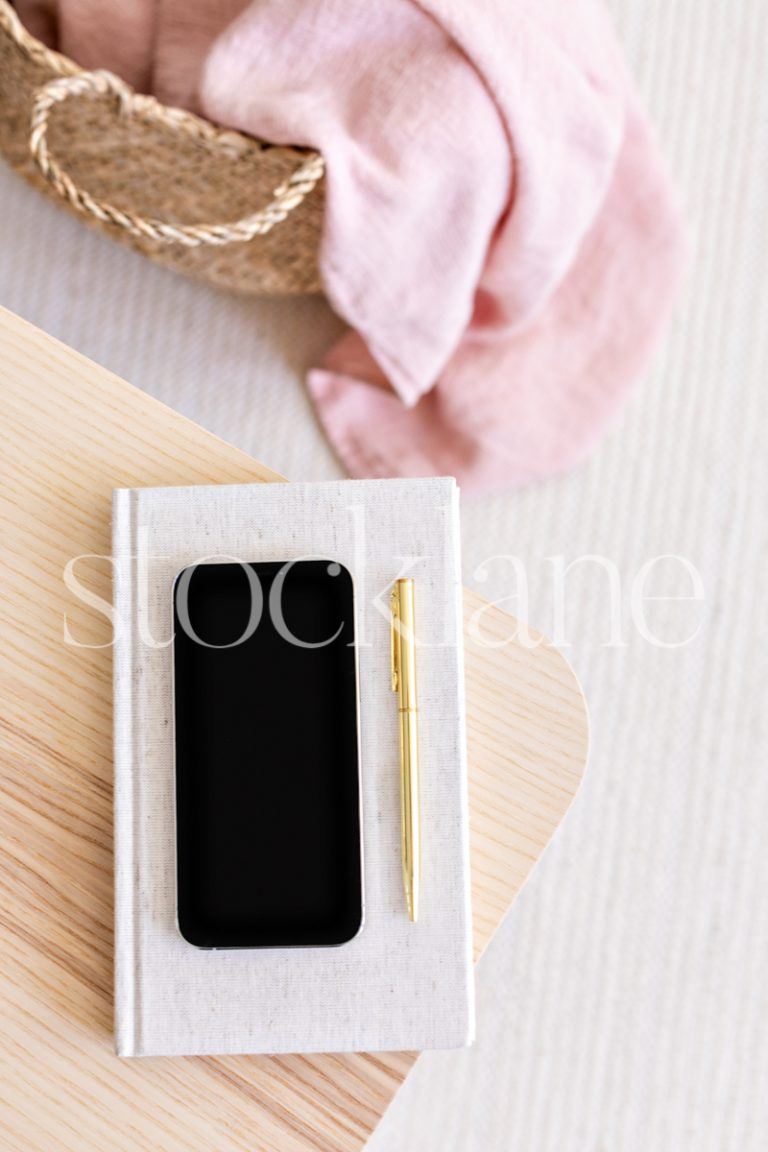 Vertical stock photo of a phone mockup in pink and neutral colors.