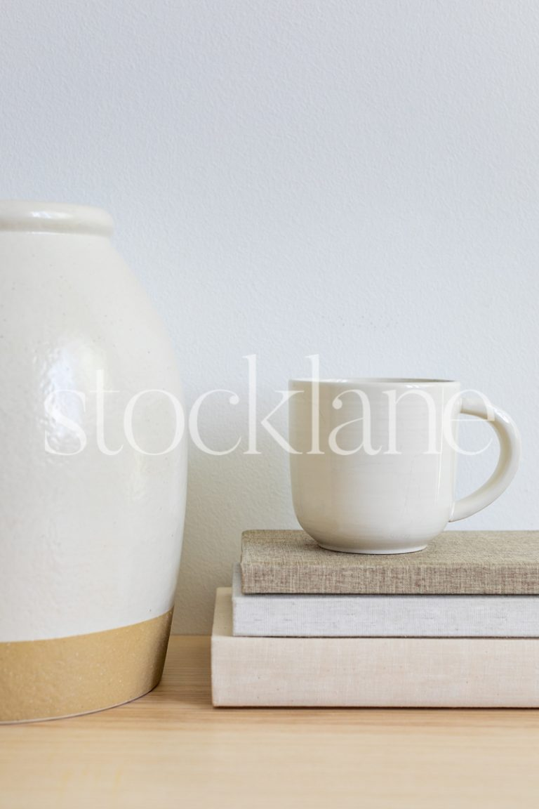 Vertical stock photo of books, a cup of coffee and a decorative vase in neutral colors.
