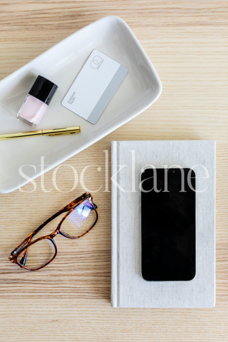 Vertical stock photo of a phone, glasses and personal items in neutral colors.