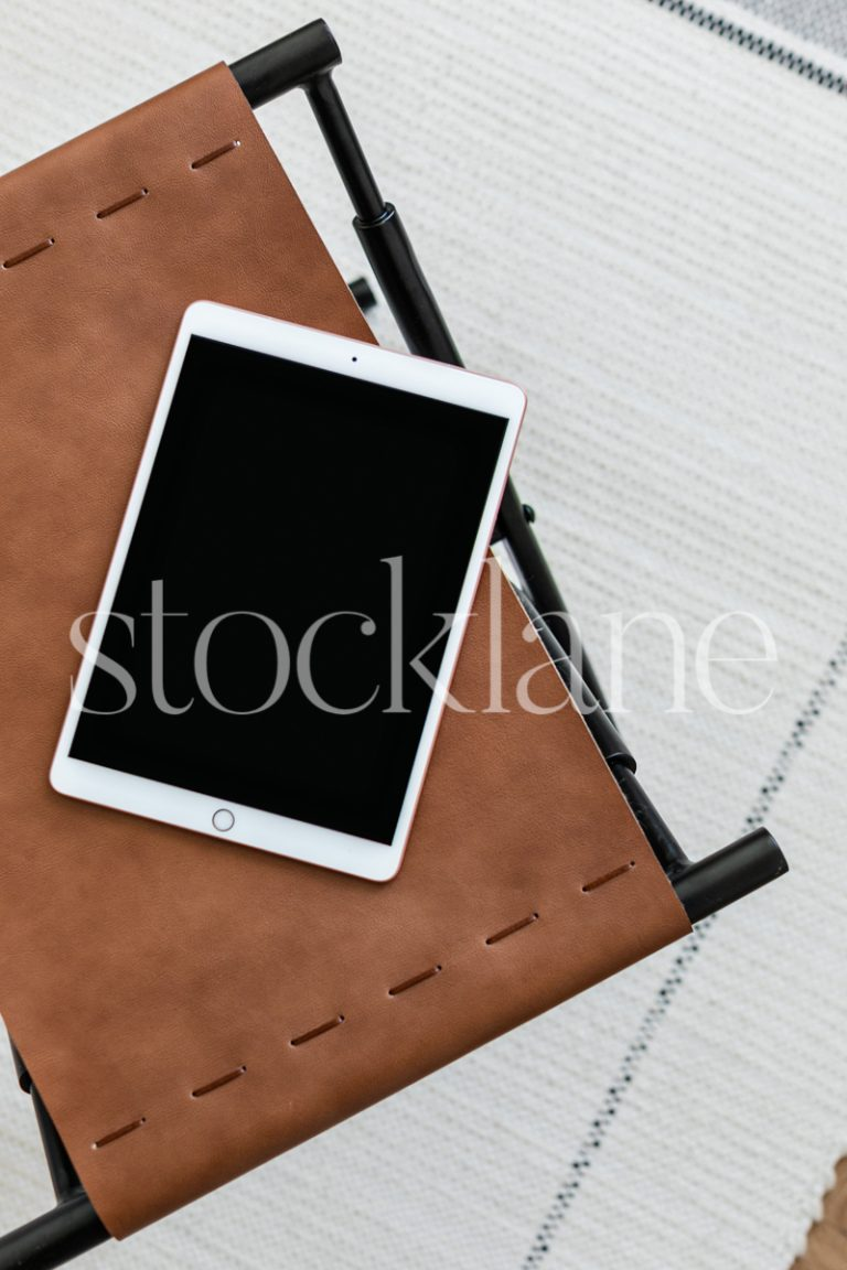 Vertical stock photo of a tablet mockup on a leather ottoman.