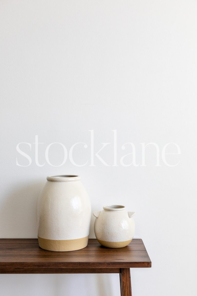 Vertical stock photo of two decorative vases in neutral colors.