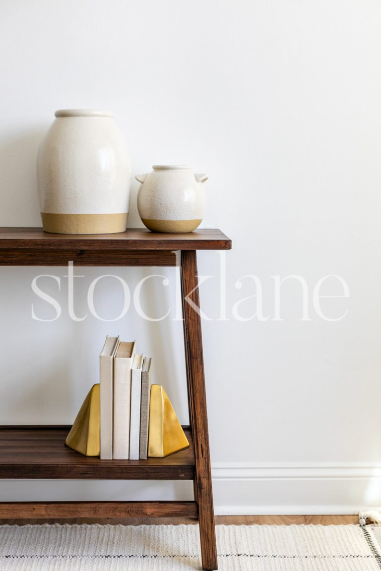 Vertical stock photo of a table with decorative items in neutral colors.