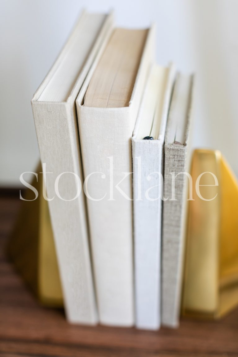 Vertical stock photo of a stack of books in neutral colors.