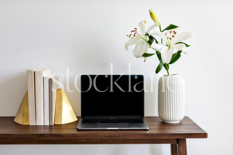 Horizontal stock photo with white asian lilies, books, and a computer