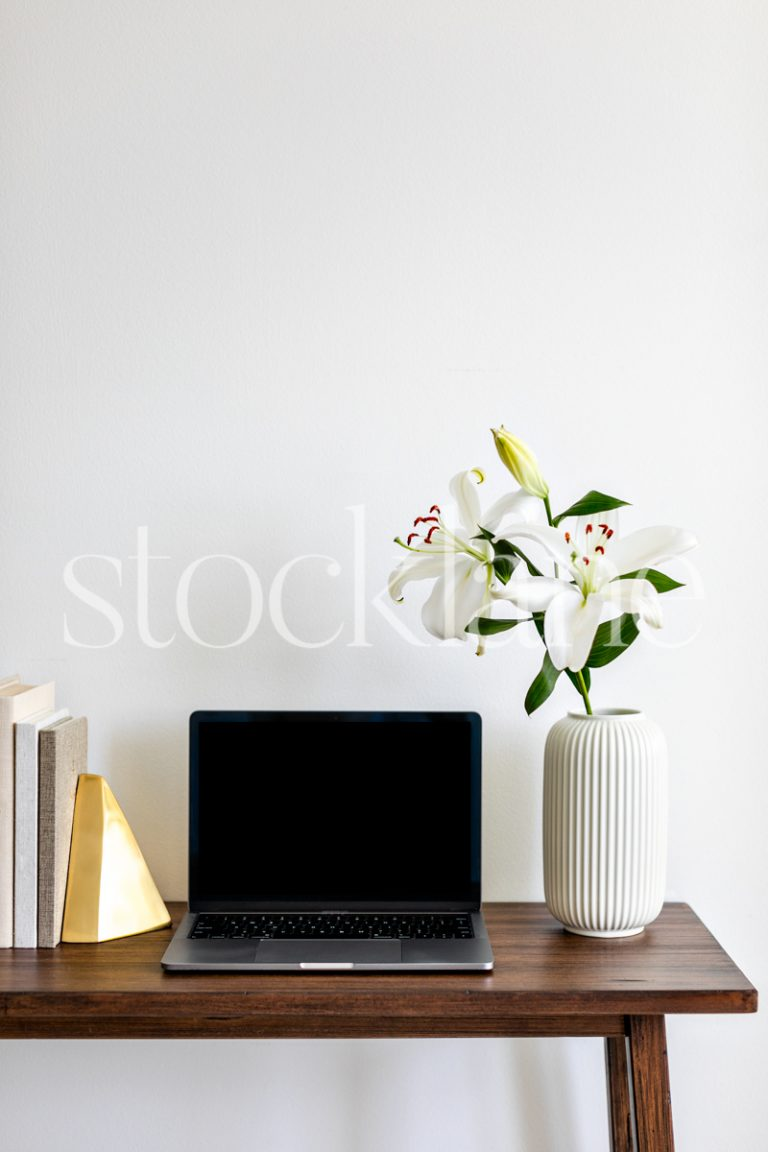 Vertical stock with white asian lilies, books, and a computer