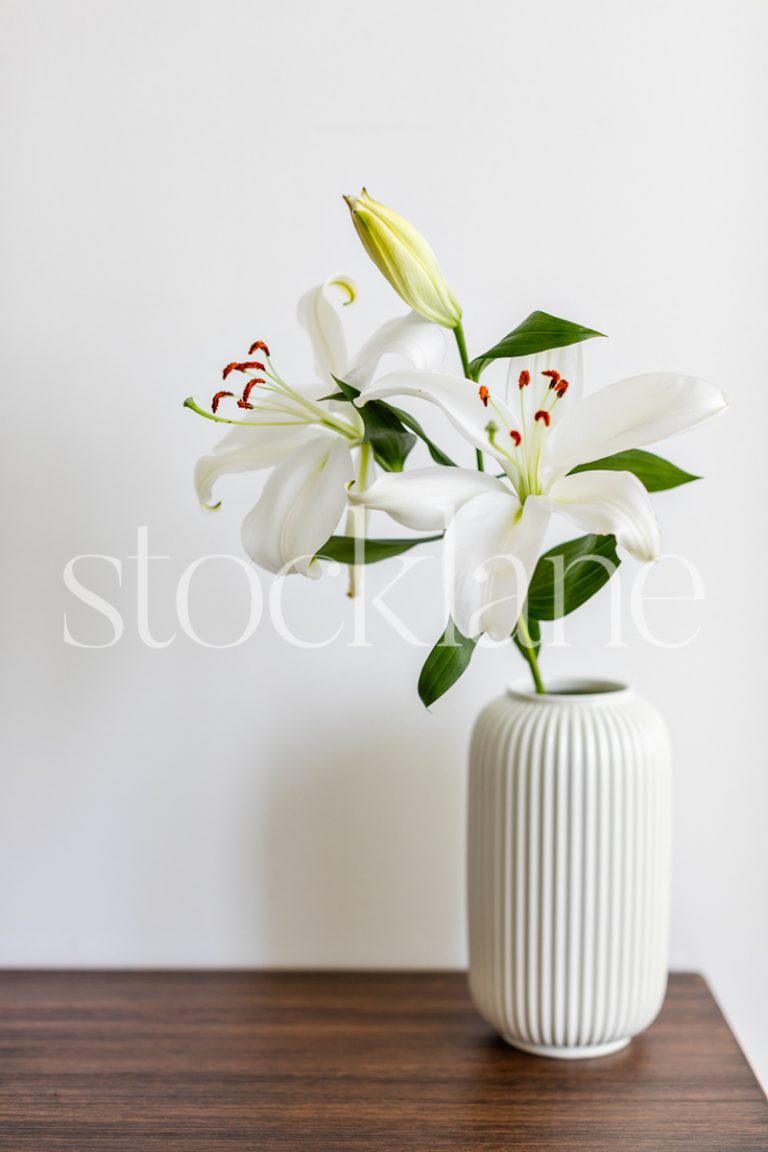 Vertical stock photo of a vase with white Asian lilies